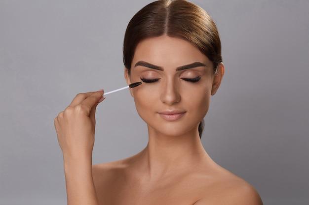 Máscara. maquillaje de belleza, piel suave y fresca y pestañas largas y gruesas y gruesas aplicando rímel con pincel cosmético. extensiones de pestañas. pestañas postizas.