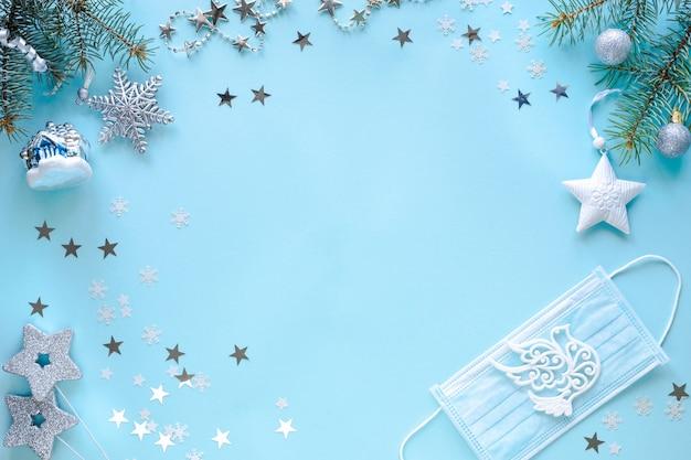 Máscara médica y adornos navideños en superficie azul