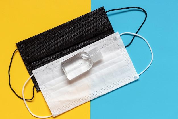 Máscara médica en blanco y negro con desinfectante sobre un fondo azul y amarillo