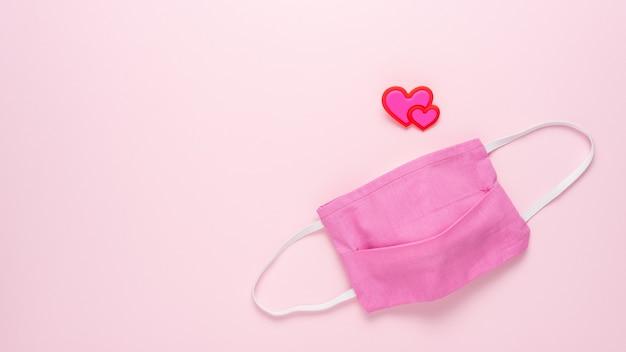 Máscara médica con corazón en superficie rosa.