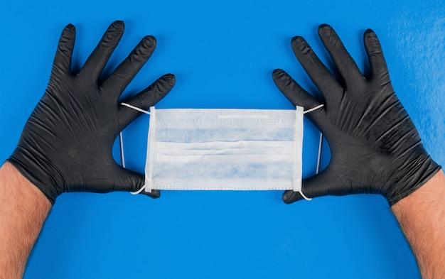 Máscara médica en manos con guantes negros. vista superior.
