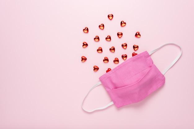 Máscara médica con pequeños corazones de cristal en superficie rosa.