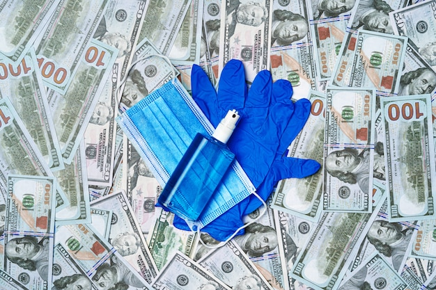 Máscara médica protectora, guantes y desinfectante en billetes de dólar estadounidense
