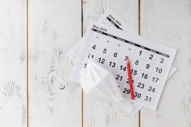 Máscara médica protectora en las hojas del calendario.