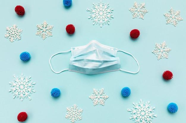 Máscara médica de vista superior y copos de nieve decorativos