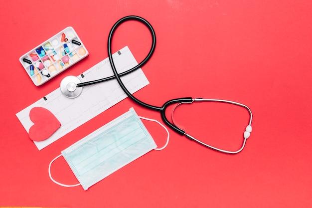 Máscara y medicamentos cerca de estetoscopio y cardiograma
