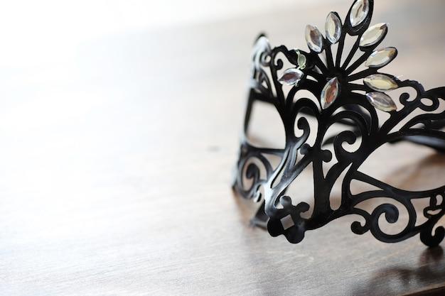 Máscara negra en el fondo de madera con espacio para texto