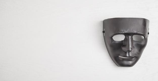 Máscara negra en la pared blanca