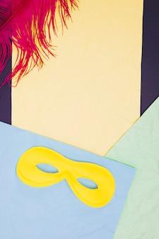 Máscara de ojo rosa y pluma amarilla contra papel de colores.