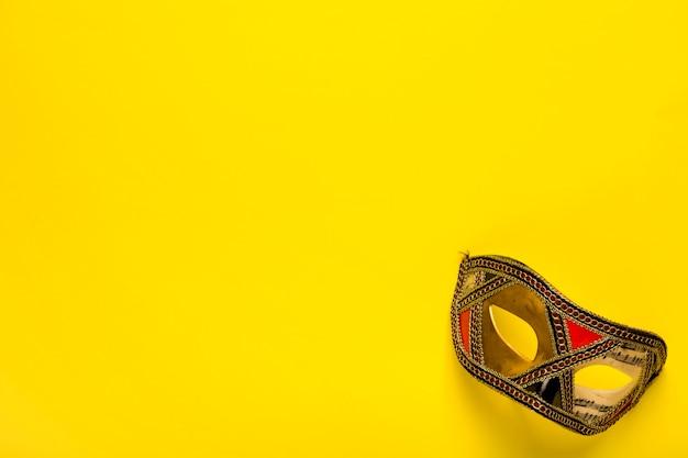 Máscara de oro sobre fondo amarillo con espacio de copia