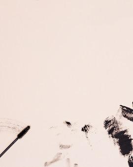 Máscara de pestañas pincel trazo sobre fondo beige