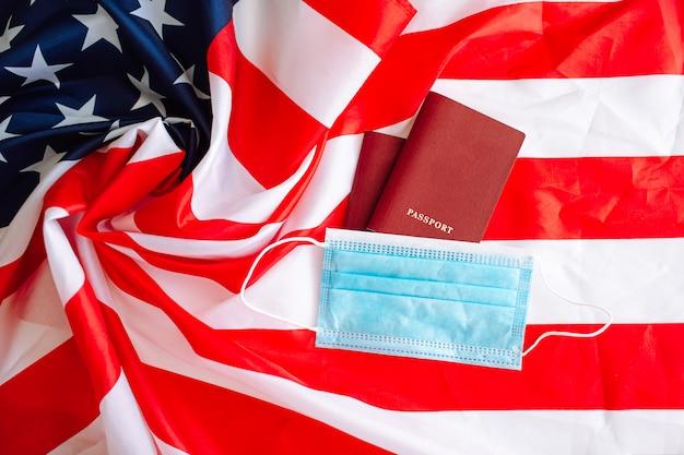 Máscara protectora médica y dos pasaportes rojos en una bandera estadounidense