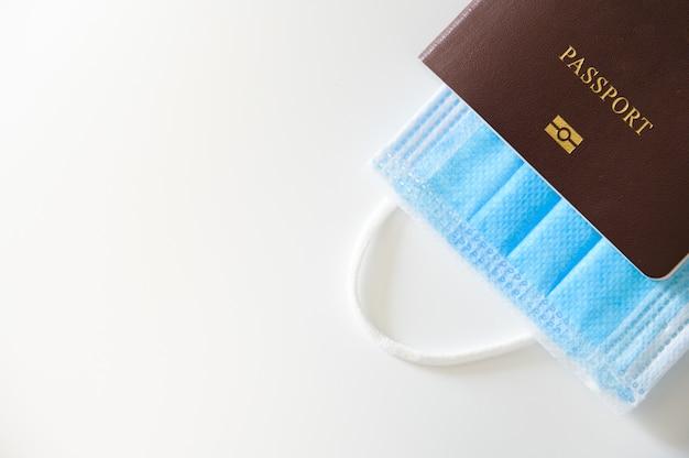 Máscara protectora médica y pasaporte. viaje conceptual, desglose del país