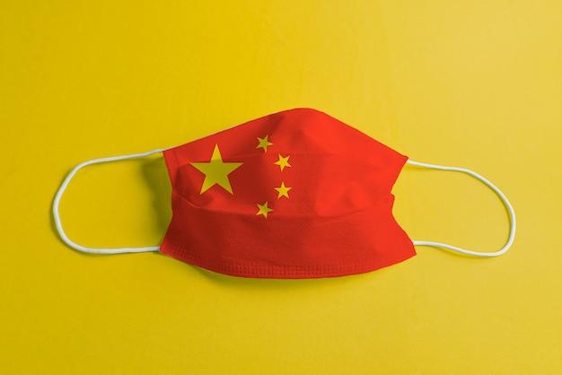 Máscara quirúrgica sobre fondo amarillo con bandera de china