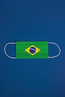 Máscara quirúrgica sobre fondo azul con bandera brasileña