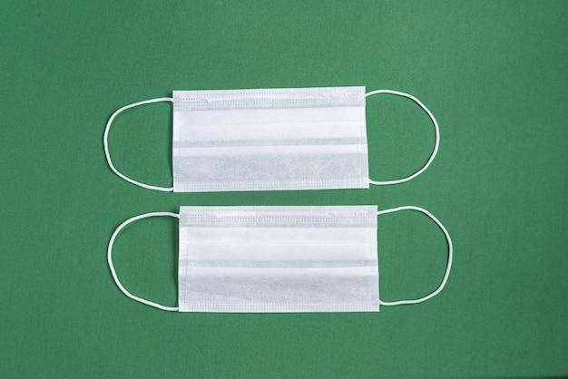 Máscara quirúrgica sobre fondo verde minimalista.