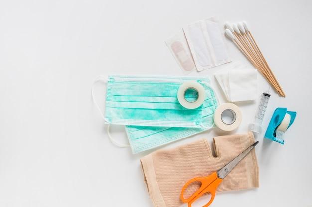 Máscara quirúrgica; vendaje; gasa; cotonetes; vendaje adhesivo y rodillera con tijera sobre fondo blanco