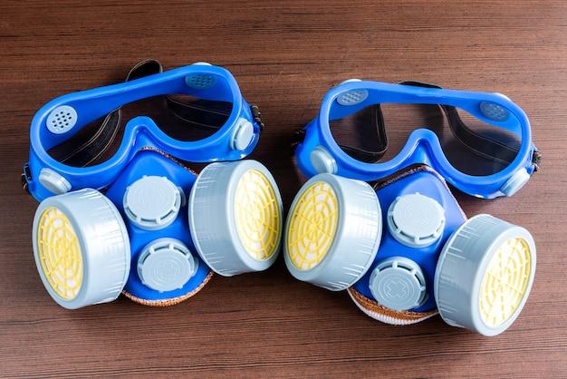 Máscara de respirador, máscara de polvo y máscara de seguridad para productos químicos industriales sobre fondo de madera.