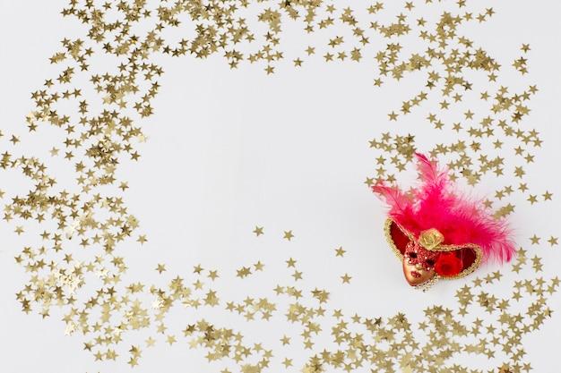 Una máscara roja de carnaval y confeti dorado alrededor