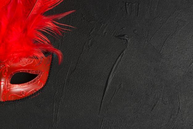 Máscara roja en la mesa oscura