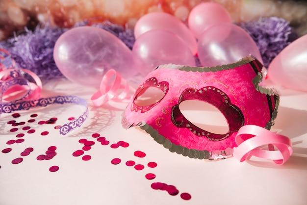 Máscara rosa de fantasía con elementos de fiesta.
