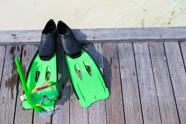 Máscara, snorkel y aletas para bucear en el embarcadero de madera.