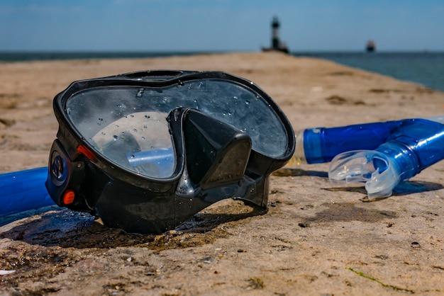 Máscara y snorkel en el muelle junto al mar, vacaciones y viajes.