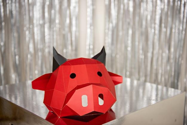 Máscara de toro de cartón rojo se encuentra en un piso plateado