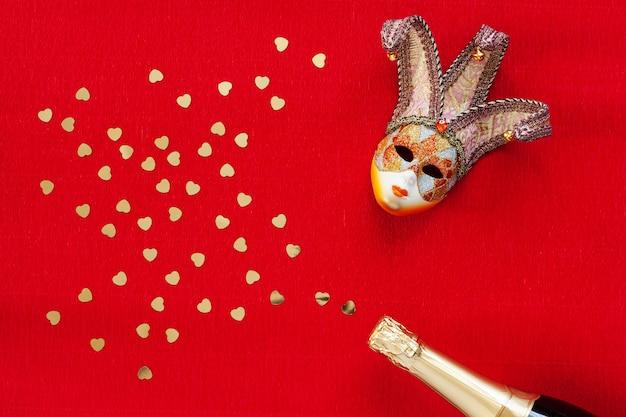 Máscara veneciana, botella de champagne con confeti corazón oro. vista superior, de cerca sobre fondo rojo
