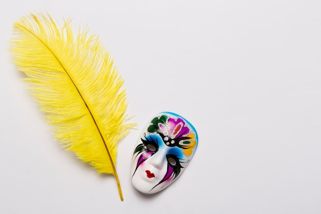 Máscara veneciana cerca de enormes plumas