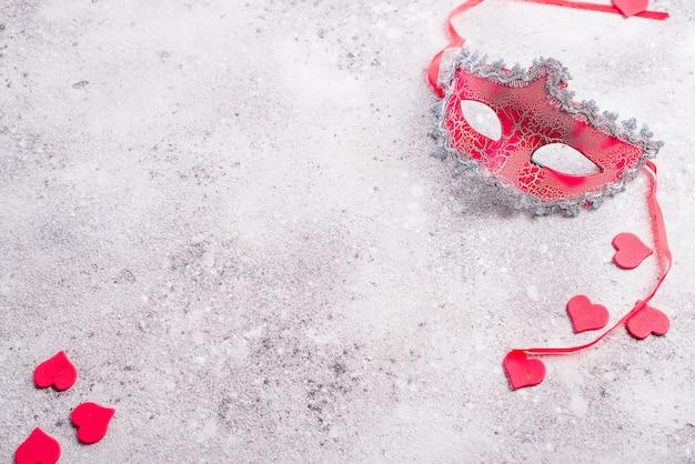 Máscara veneciana y corazones de las tarjetas del día de san valentín en el fondo de piedra. concepto de cita a ciegas, copia espacio