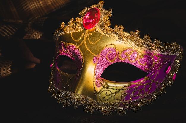 Máscara veneciana dorada y rosa sobre un fondo oscuro