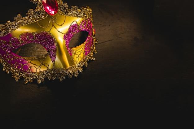 Máscara veneciana dorada sobre un fondo oscuro e1cadec796b