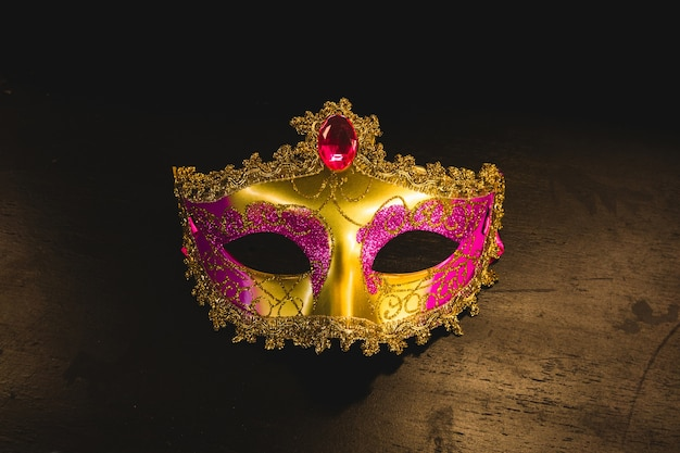 Máscara veneciana dorada sobre una mesa de madera efc139518af