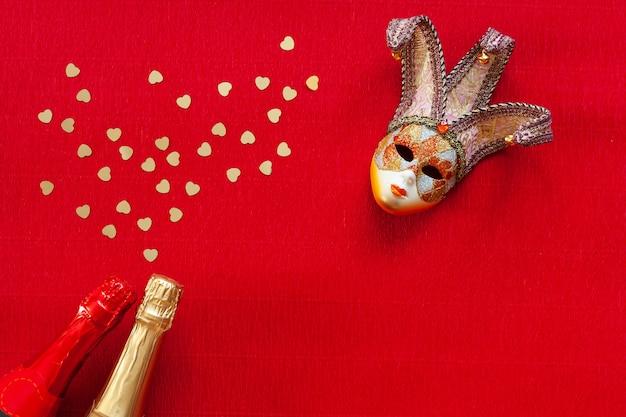 Máscara veneciana, dos botellas de champagne con confeti de oro y corazón. vista superior, de cerca sobre fondo rojo