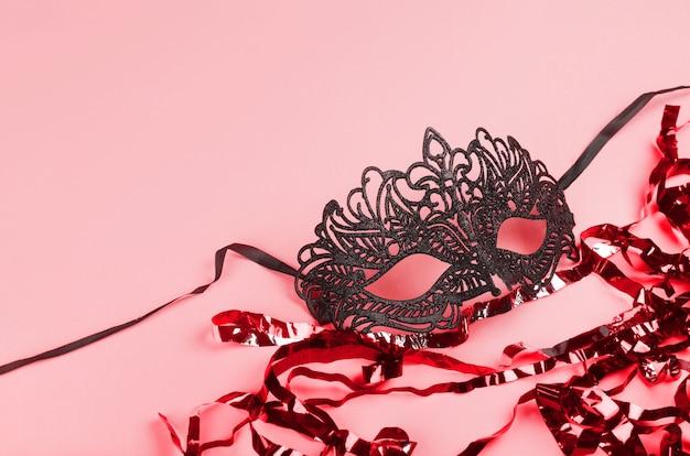 Máscara veneciana negra delicada sobre fondo rojo festivo con polvo de hadas