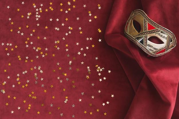 Máscara veneciana sobre una tela roja con confeti de estrellas al lado