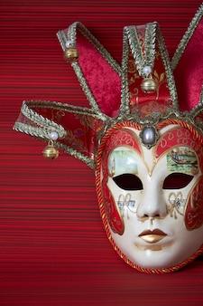 Máscara veneciana tradicional de carnaval con una rica decoración sobre un fondo rojo, enfoque selectivo