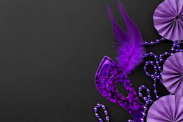 Máscara violeta elegante y decoraciones sobre fondo oscuro