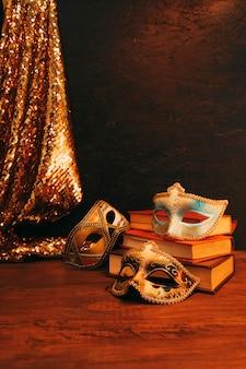 Máscaras azules y doradas con libros antiguos y textiles de lentejuelas brillantes en el escritorio de madera
