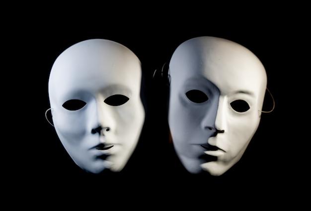 Máscaras blancas de hombre y mujer sobre un fondo negro