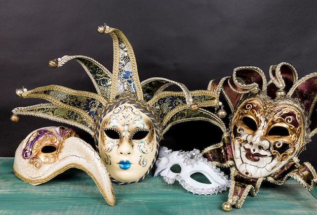 Máscaras venecianas del carnaval en superficie de madera verde contra fondo oscuro