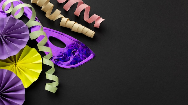 Máscaras violetas y cintas sobre fondo oscuro