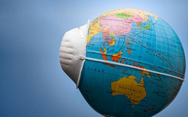 Mascarilla alrededor de un globo terráqueo en vista lateral