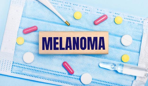 En una mascarilla desechable de color azul claro hay tabletas, un termómetro, una ampolla y un bloque de madera con el texto melanoma. concepto medico