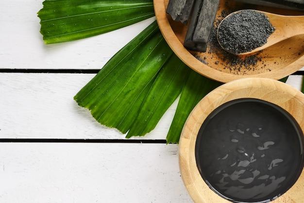 Mascarilla facial y exfoliante con polvo de carbón activado en mesa de madera