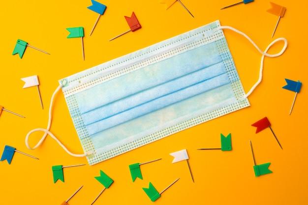 Mascarilla médica y clips de papel sobre fondo amarillo