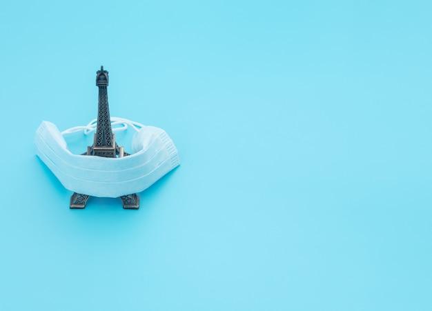 La mascarilla médica cubre la atracción de viajes sobre fondo azul.
