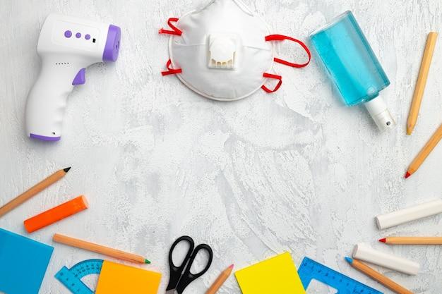 Mascarilla médica, desinfectante de manos y artículos de papelería en la vista superior de fondo con textura blanca