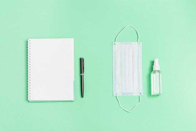 Mascarilla médica facial, desinfectante para manos, cuaderno, bolígrafo.